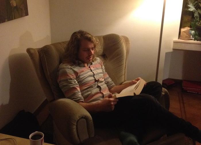Andy Leenen in zijn stoel, met koffie en een boek. Foto: Sem Delaere