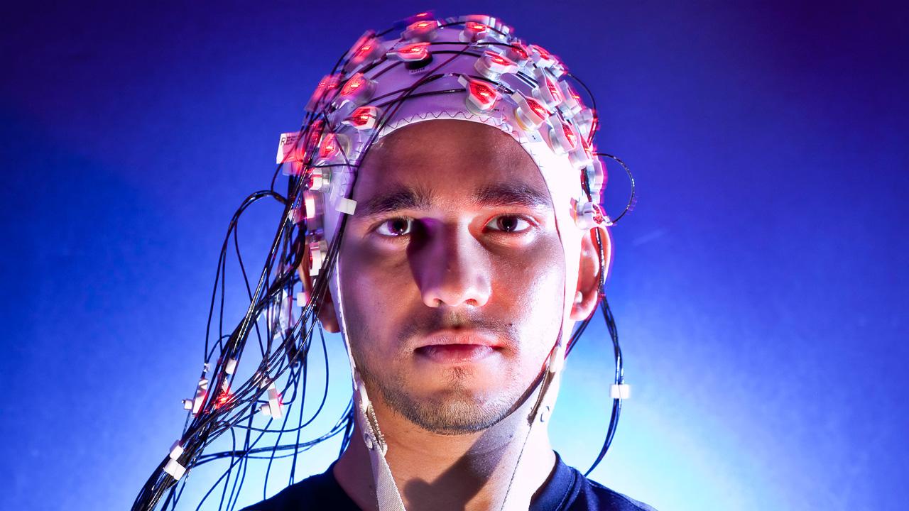 Een man met een EEG-muts op zijn hoofd, via