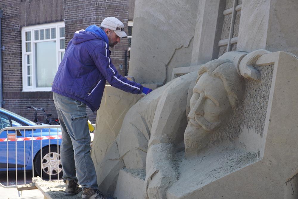 Zandkunstenaar Aleksei Rybak bevrijdt Hugo de Groot uit een berg zand.